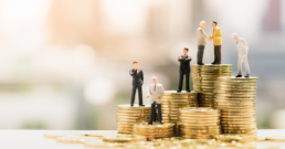 Miniature people: Small businessmen standing on stack of coins | Fixed-Price Implementation