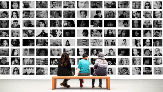 3 people sitting on a bench look at a poster made up multiple pictures of new users
