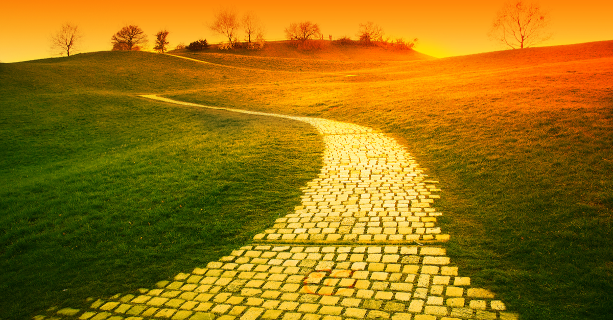 Orange sunset over hill with paved a yellow brick road